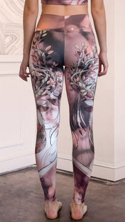 Back view of model wearing full length leggings with a deer on it. They are a purple and orange color with tree branches as the antlers and birds on the antlers