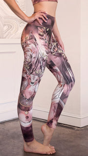 Right  side view of model wearing full length leggings with a deer on it. They are a purple and orange color with tree branches as the antlers and birds on the antlers