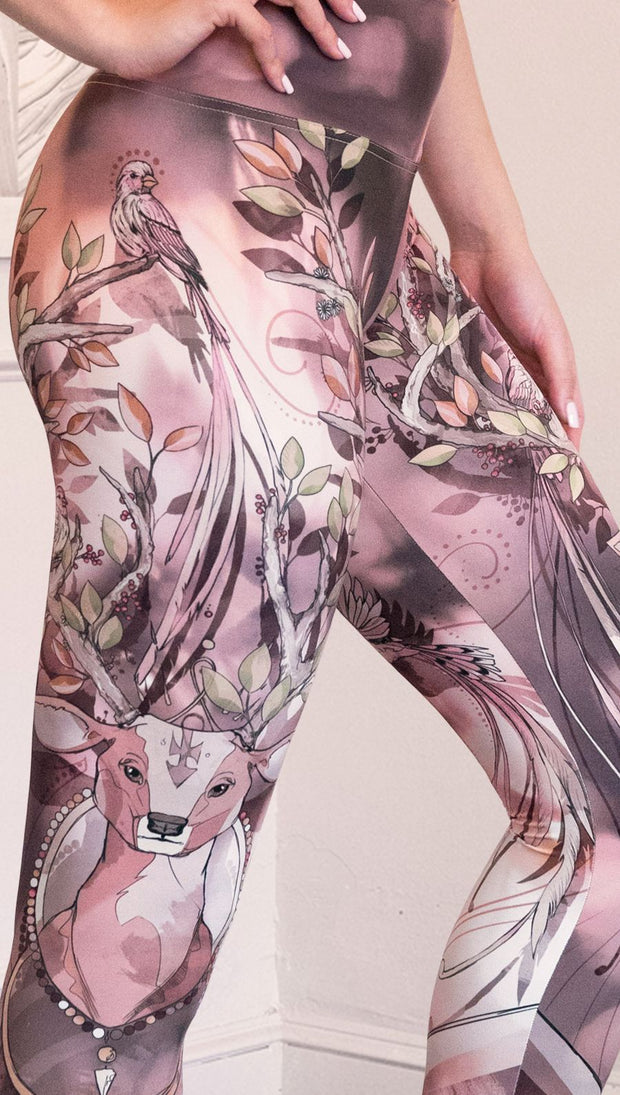 Zoomed in right view of model wearing full length leggings with a deer on it. They are a purple and orange color with tree branches as the antlers and birds on the antlers
