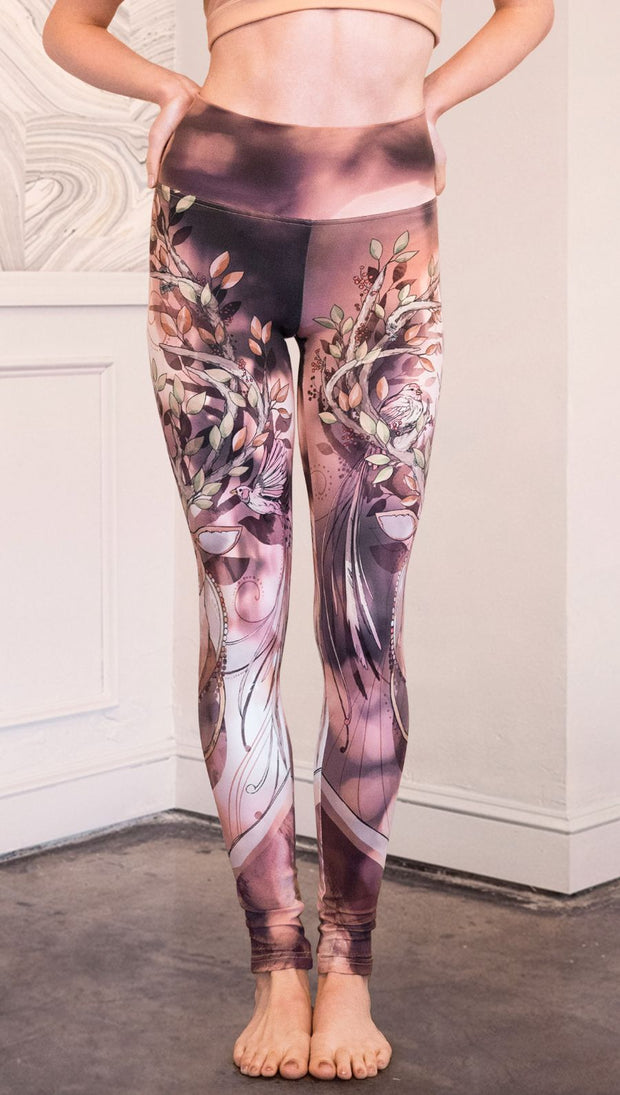 Front view of  model wearing full length athleisure leggings with a deer on it. They are a purple and orange color with tree branches as the antlers and birds on the antlers