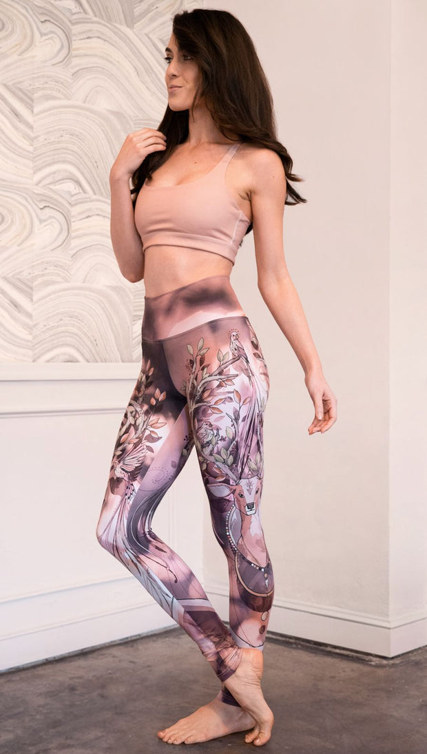 Slightly turned left view of model wearing full length leggings with a deer on it. They are a purple and orange color with tree branches as the antlers and birds on the antlers
