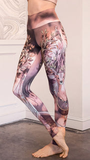 Left view of model wearing full length leggings with a deer on it. They are a purple and orange color with tree branches as the antlers and birds on the antlers