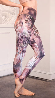 Right view of model wearing full length leggings with a deer on it. They are a purple and orange color with tree branches as the antlers and birds on the antlers