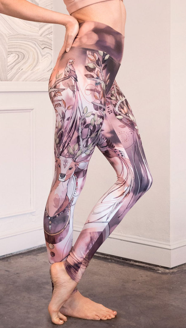 Right view of model wearing full length athleisure leggings with a deer on it. They are a purple and orange color with tree branches as the antlers and birds on the antlers