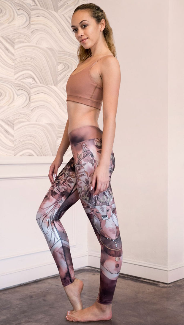 Zoomed out left side view of model wearing full length leggings with a deer on it. They are a purple and orange color with tree branches as the antlers and birds on the antlers