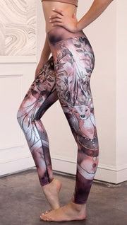 Left side view of model wearing full length triathlon leggings with a deer on it. They are a purple and orange color with tree branches as the antlers and birds on the antlers