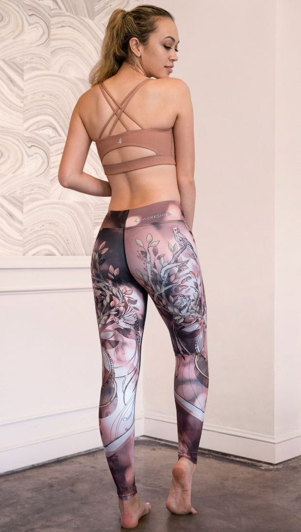 Slightly turned back view of model wearing full length leggings with a deer on it. They are a purple and orange color with tree branches as the antlers and birds on the antlers