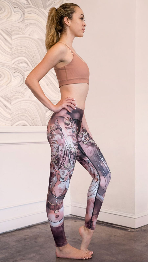 Zoomed out right side view of model wearing full length triathlon leggings with a deer on it. They are a purple and orange color with tree branches as the antlers and birds on the antlers