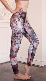 Right side view of model wearing full length triathlon leggings with a deer on it. They are a purple and orange color with tree branches as the antlers and birds on the antlers