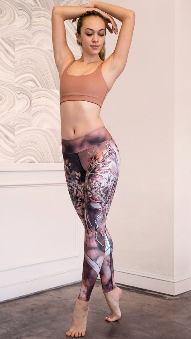 Slightly turned front view of model wearing full length leggings with a deer on it. They are a purple and orange color with tree branches as the antlers and birds on the antlers
