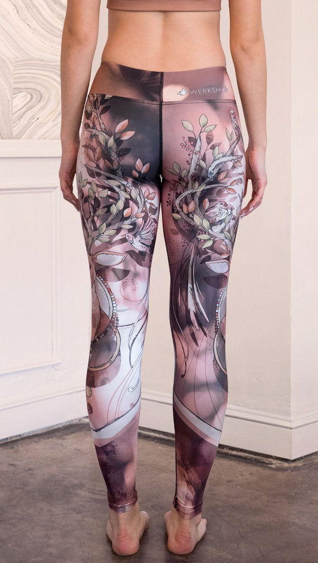 Back view of model wearing full length triathlon leggings with a deer on it. They are a purple and orange color with tree branches as the antlers and birds on the antlers