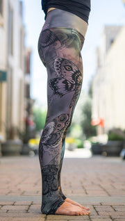 close up right side view of model wearing mashup gothic themed printed full length leggings