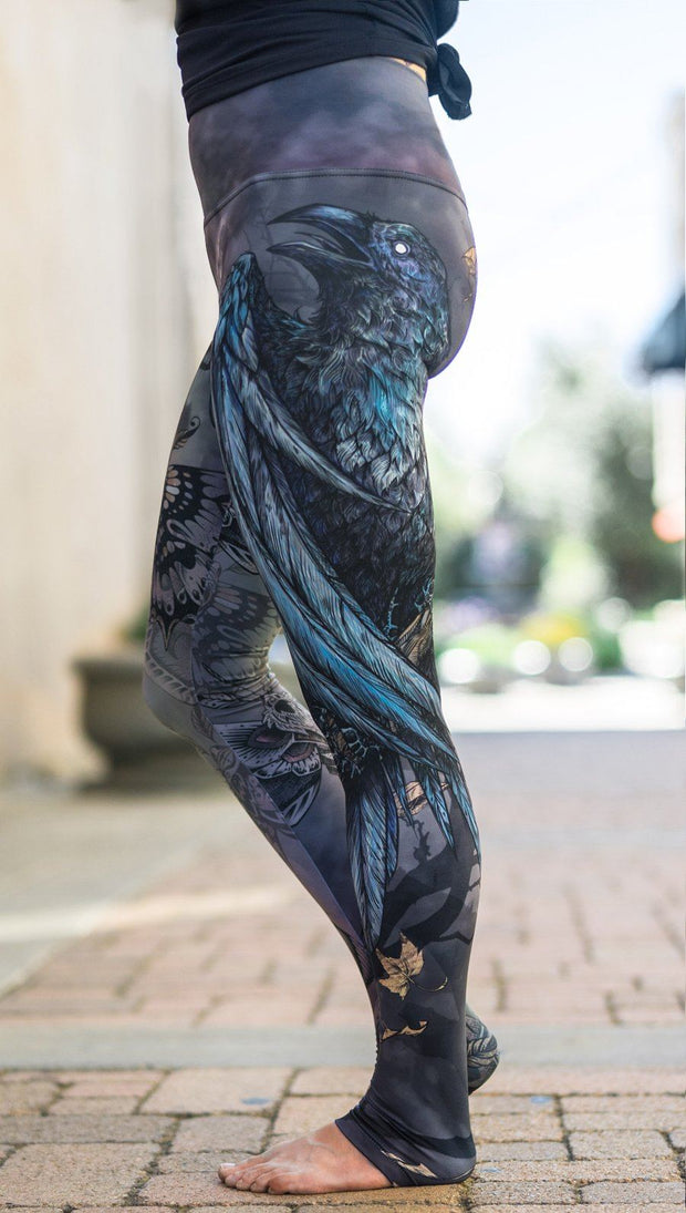 close up left side view of model wearing mashup gothic themed printed full length leggings