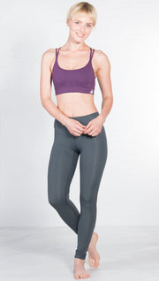 front view of model wearing seamless purple sports bra with criss cross straps and back mesh detail