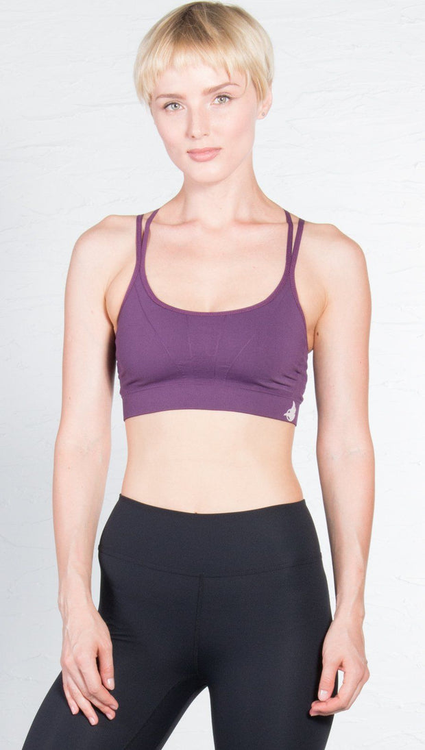 closeup front view of model wearing seamless purple sports bra with criss cross straps and back mesh detail