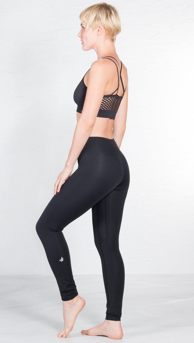 left side view of model wearing black sports bra with matching leggings