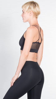 left side closeup view of model wearing black sports bra with matching leggings