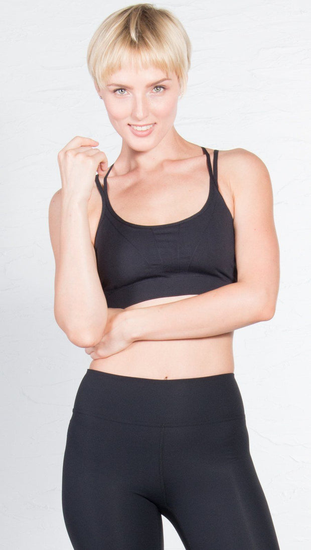 closeup front view of model wearing black sports bra with matching leggings