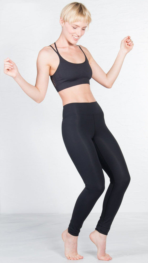 slightly turned front view of model wearing black sports bra with matching leggings