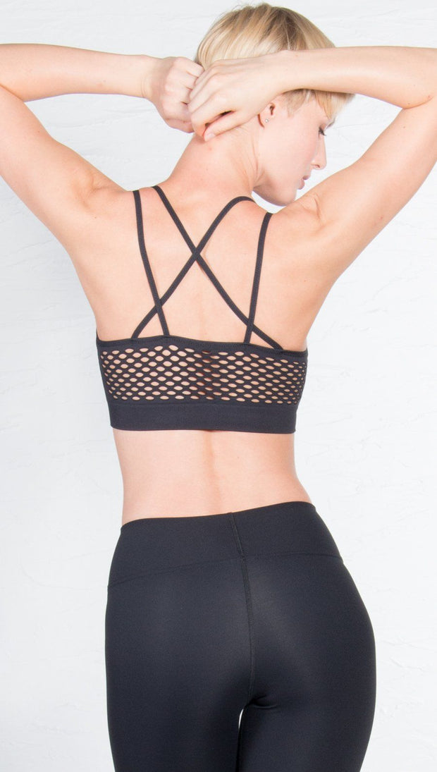 back view of model wearing black sports bra with matching leggings