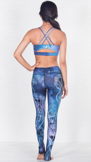 back view of model wearing blue water color inspired printed sports bra