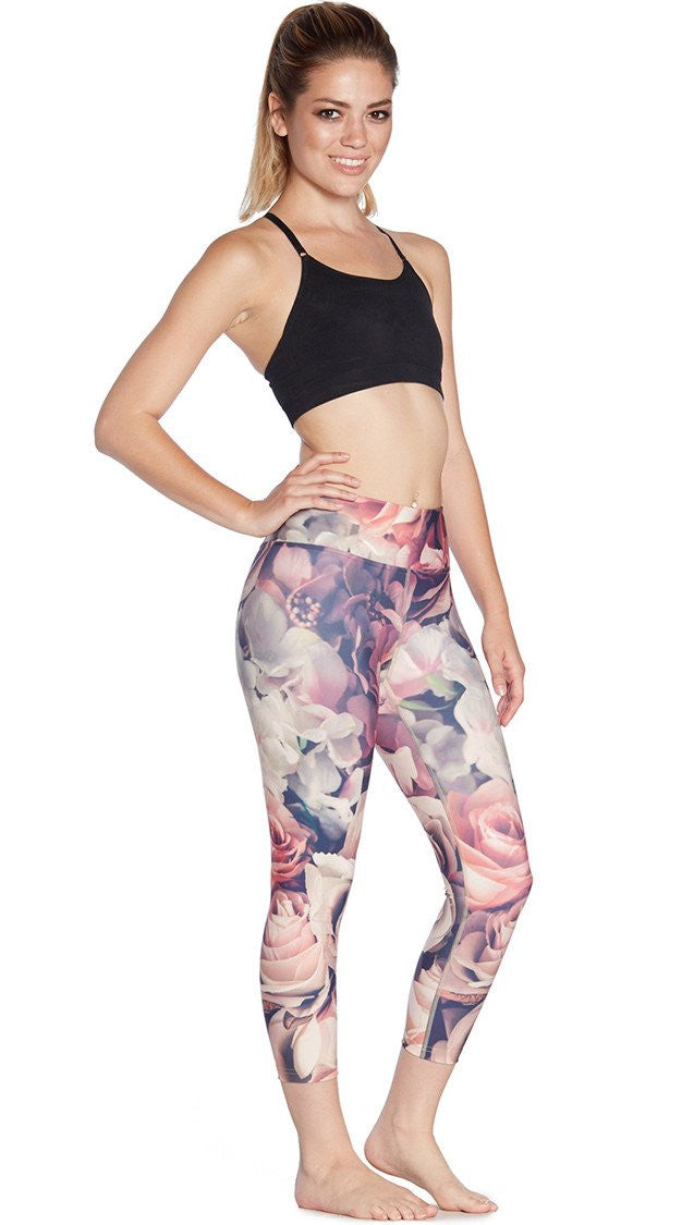 close up right side view of model wearing pink floral printed capri leggings