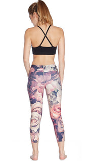 back view of model wearing pink floral printed capri leggings