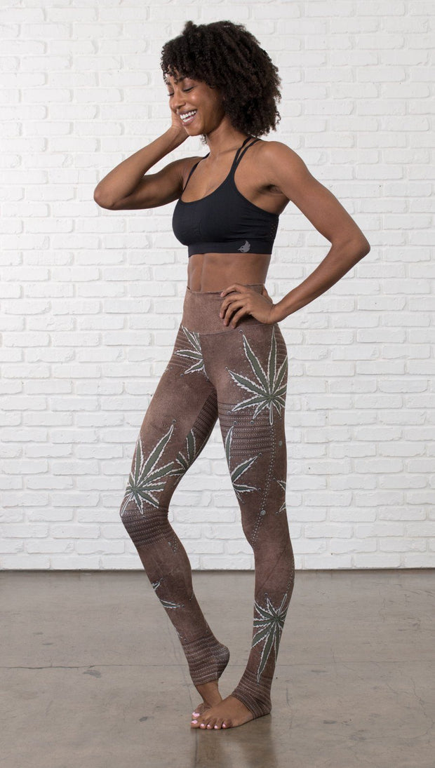left side view of model wearing cannabis leaf printed full length leggings