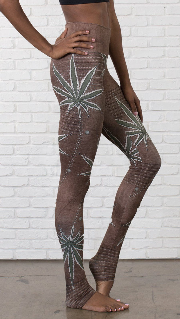 close up right side view of model wearing cannabis leaf printed full length leggings