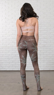 back view of model wearing cannabis leaf printed full length leggings