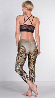 back view of model wearing capri leggings with printed leopard design