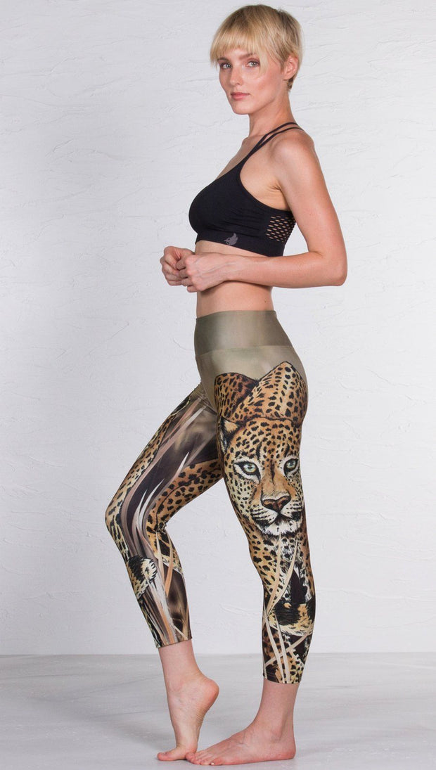 left side view of model wearing capri leggings with printed leopard design