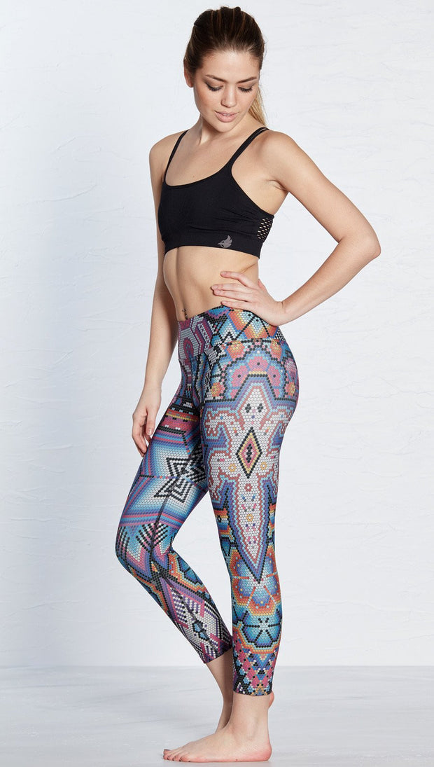 left side view of model wearing latin beads themed printed capri leggings with lizard design