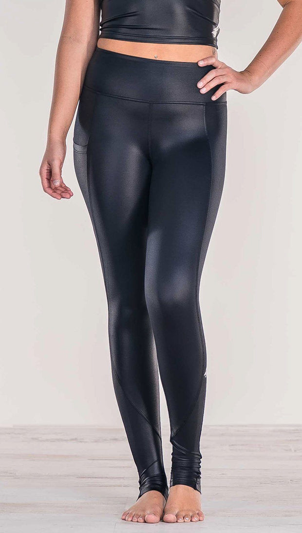 Close up front view of model wearing shiny black full length leggings with right side pocket