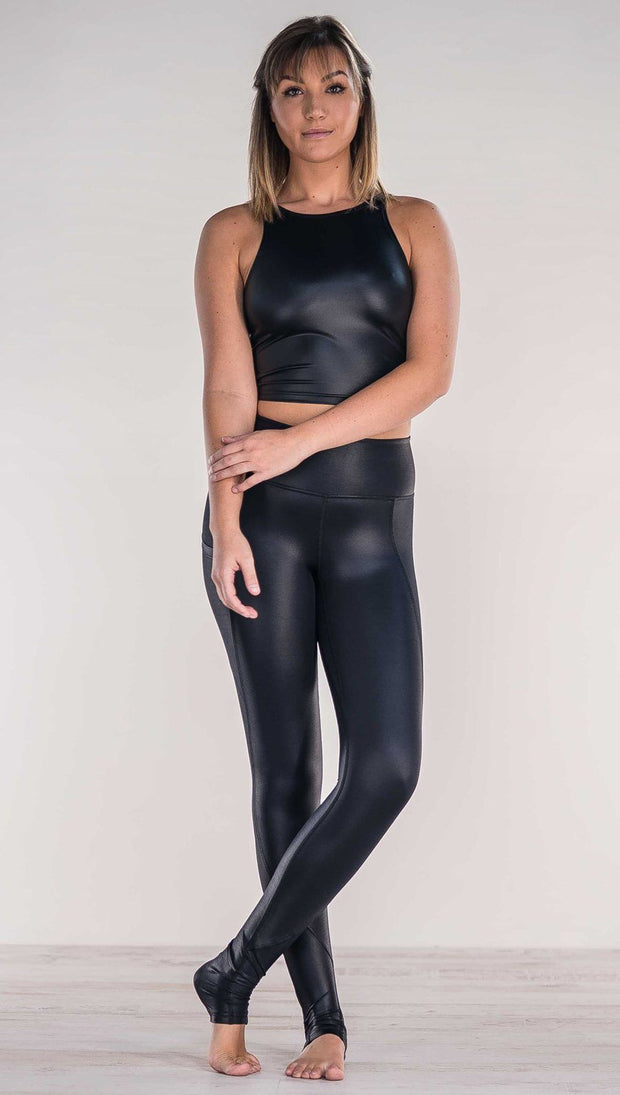 Front view of model crossing ankles wearing shiny black full length leggings with right side pocket
