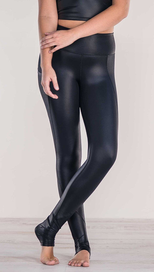 Close up front view of model crossing ankles wearing shiny black full length leggings with right side pocket