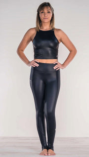 Front view of model wearing shiny black full length leggings with right side pocket