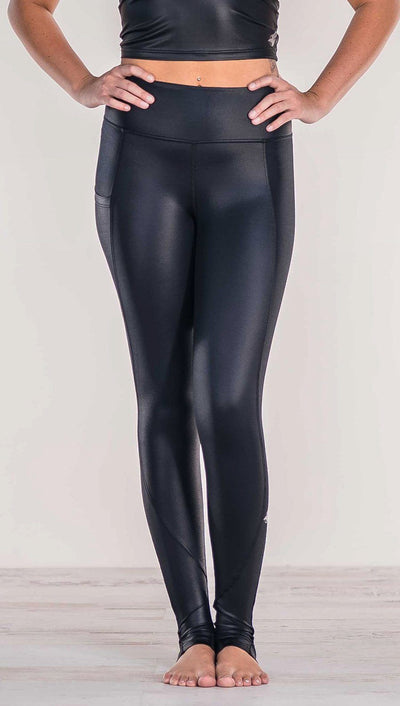 Front View of model wearing shiny black leggings with pocket on the wearers right hip.