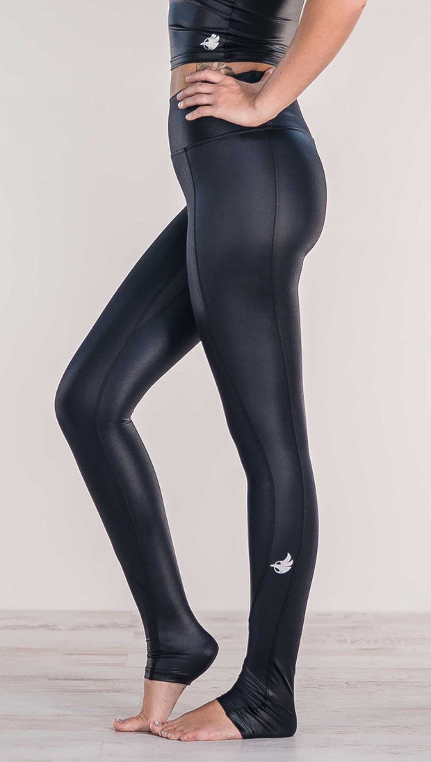Close up side view of model wearing shiny black full length leggings with right side pocket
