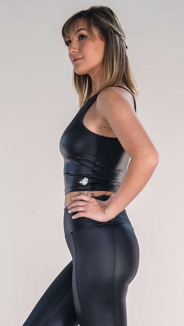 Side view of model wearing shiny black sleeveless top