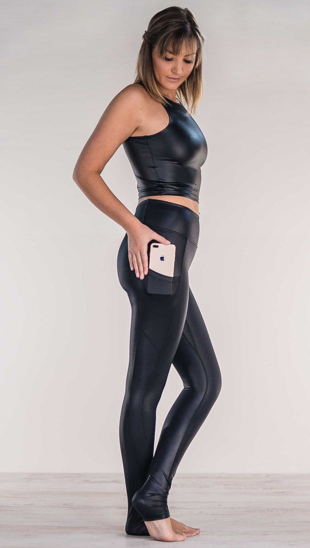 Side view of model wearing shiny black leggings putting iphone into right side pocket