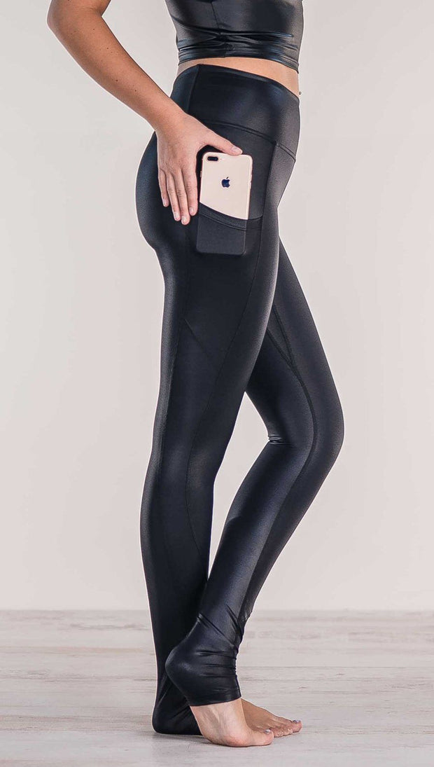 Close up side view of model wearing shiny black full length leggings putting iPhone into right side pocket