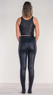 Rear view of model wearing shiny black full length leggings with right side pocket