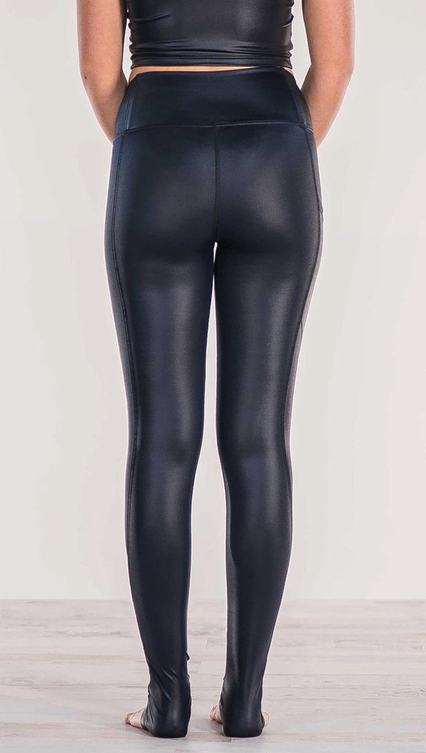 Close up rear view of model wearing shiny black full length leggings with right side pocket