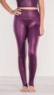 Close up front view of model wearing shiny eggplant purple colored full length leggings with right side pocket