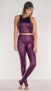 Front view of model crossing ankles wearing shiny eggplant purple colored full length leggings with right side pocket