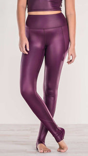 Close up front view of model crossing ankles wearing shiny eggplant purple colored full length leggings with right side pocket