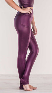 Close up side view of model wearing shiny eggplant purple colored full length leggings with right side pocket
