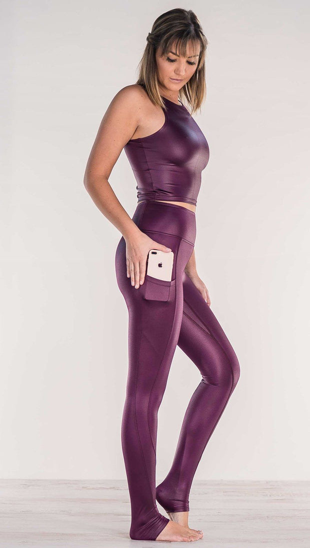 Side view of model wearing shiny eggplant purple colored full length leggings putting iphone into right side pocket