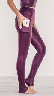 Close up side view of model wearing shiny eggplant purple colored full length leggings putting iphone into right side pocket